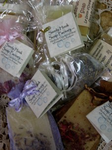 An assortment of natural soap favours are pictured with organic botanicals and thank you cards for wedding and shower guests.  Attractively presented soap in different coloured fabric bags with satin ribbons wonderful inexpensive quality wedding favour gifts and shower favour gifts.