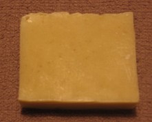 A single beige coloured bar of pure natural soap is displayed on a light brown facecloth.  Organic botanicals can be seen throughout the vegan organic hemp oil soap made by hand in Canada by the Sandy Hook Soap Factory which is an inexpensive and wonderful shampoo, body and face bar.