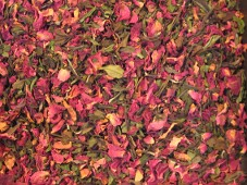A close up picture of a beautiful organic Rose Petal Tea is displayed from this Canadian tea maker.  Vibrant organic red rose petals blend with pink rose petals and complimented with fresh pick white tea leaves.