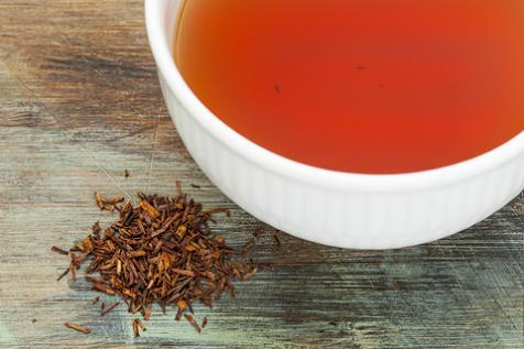 A lovely cup of red tea is displayed on a distressed wood table with loose leaf red rooibos.  All of the Red Teas featured at Organic Teas Canada are caffeine free.