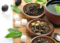 A warm and enticing display of loose leaf black teas in wooden bowls with sugar cubes and blackberries.  Organic Teas Canada offers several varieties of organic and fair trade certified Black Teas.