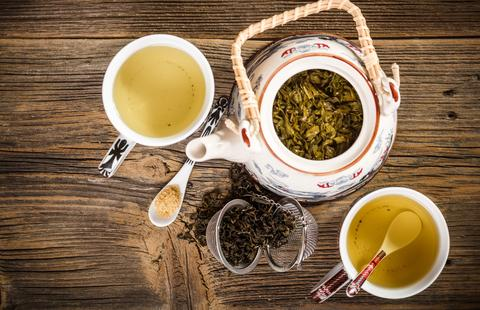 A lovely presentation of green tea in a teapot, cups and spoons and a tea ball open with loose leaf tea tumbling out onto a wooden plank table.  Organic Teas Canada presents an excellent selection of all organic Green Tea with several varieties also certified fair trade.