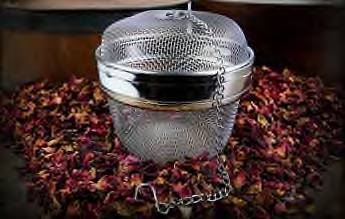 A beautiful presentation of a shiny new all stainless steel spice and tea ball with herbs surrounding it available through Organic Teas Canada.