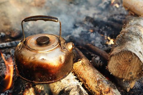 A well used copper kettle sits in the centre of a smokey campfire at the head of instructions on how to brew the perfect cup of tea at Organic Teas Canada.