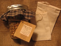 An earthy and natural presentation on burlap of a mason jar with a green checked fabric decorative cap and two organic cotton mulling bags to mull the assorted organic mulling spices in the jar.  Another great, inexpensive organic gift idea from Organic Teas Canada dot com.